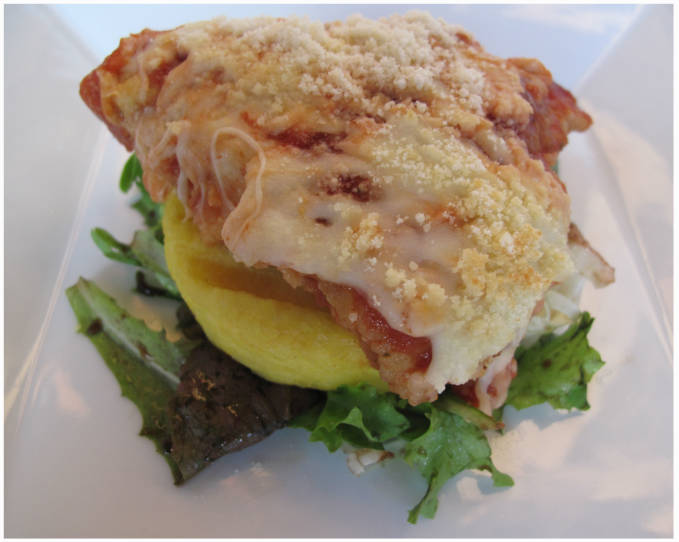 Finished chicken parmesan with polenta and a mixed-green salad