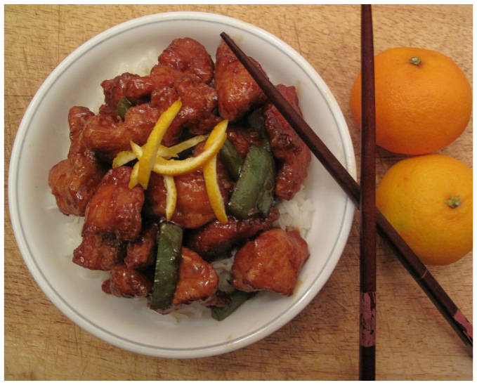 Sweet and sour orange chicken with green peppers, rice, and orange zest.
