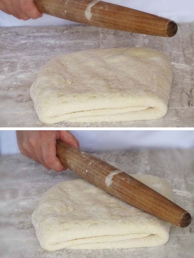 Hitting the croissant dough with a rolling pin to distribute the beurrage (butter and flour block)