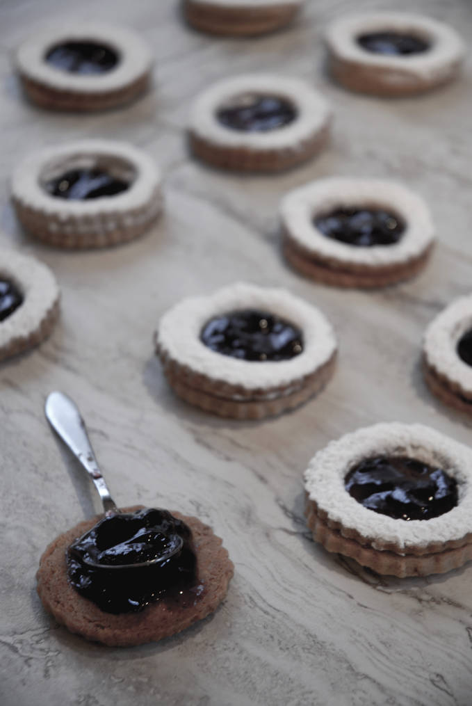 Pecan linzer cookies filled with raspberry jam and dusted with icing sugar. Click for the recipe!