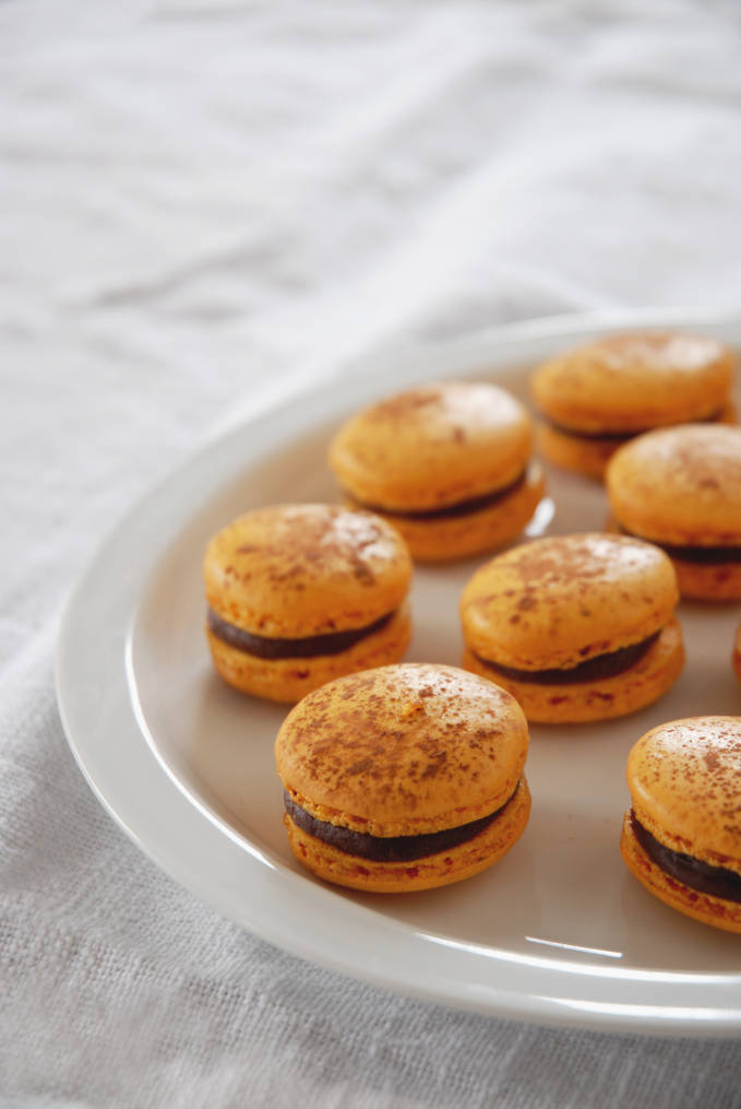 Passion fruit &  milk chocolate French macarons on a plate... but wouldn't they be better in your mouth? Click to get the recipe!