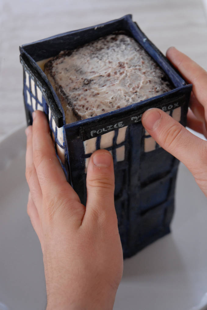 Attaching TARDIS cake sides--click to see the full photo tutorial so YOU CAN MAKE YOUR OWN DOCTOR WHO TARDIS CAKE! #diy
