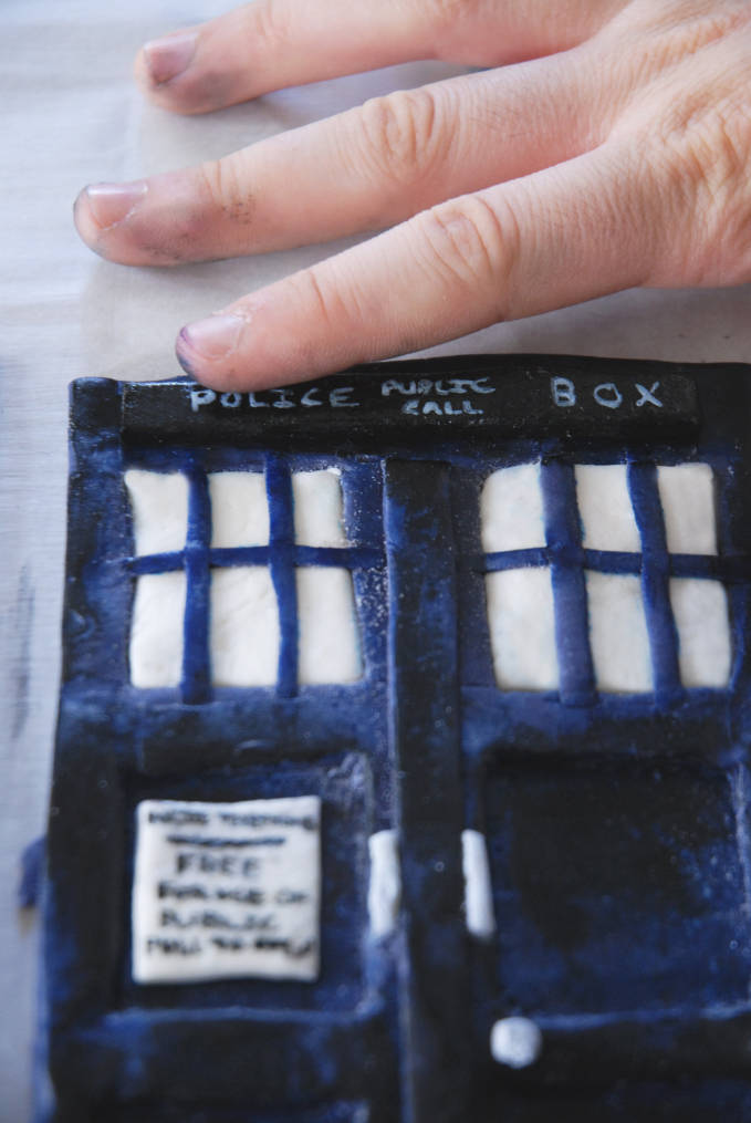 Attaching police public call box sign to Doctor Who TARDIS cake--click to see the full photo tutorial so YOU CAN MAKE YOUR OWN DOCTOR WHO TARDIS CAKE! #diy