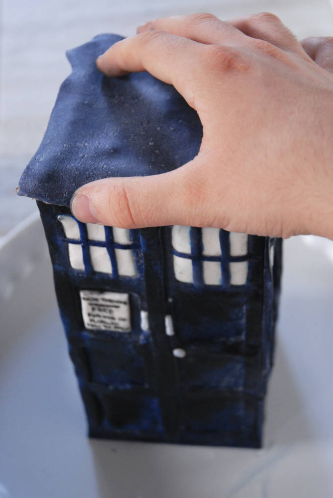 Attaching TARDIS modelling chocolate roof to cake--click to see the full photo tutorial so YOU CAN MAKE YOUR OWN DOCTOR WHO TARDIS CAKE! #diy