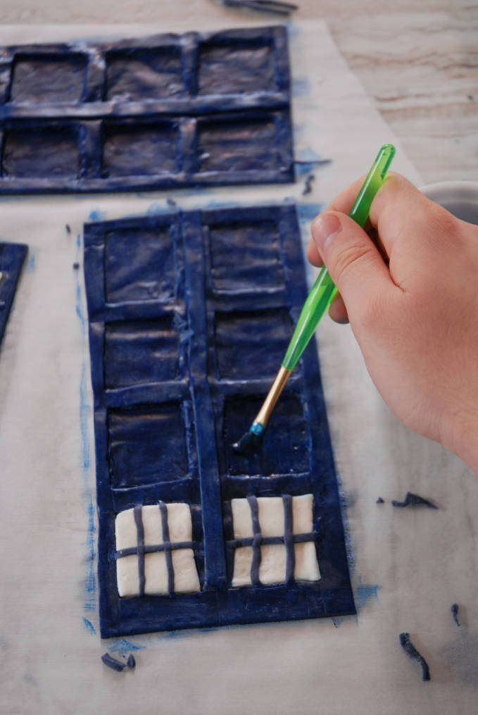 Painting the Doctor Who TARDIS cake sides with blue and black food colouring--click to see the full photo tutorial so YOU CAN MAKE YOUR OWN DOCTOR WHO TARDIS CAKE! #diy