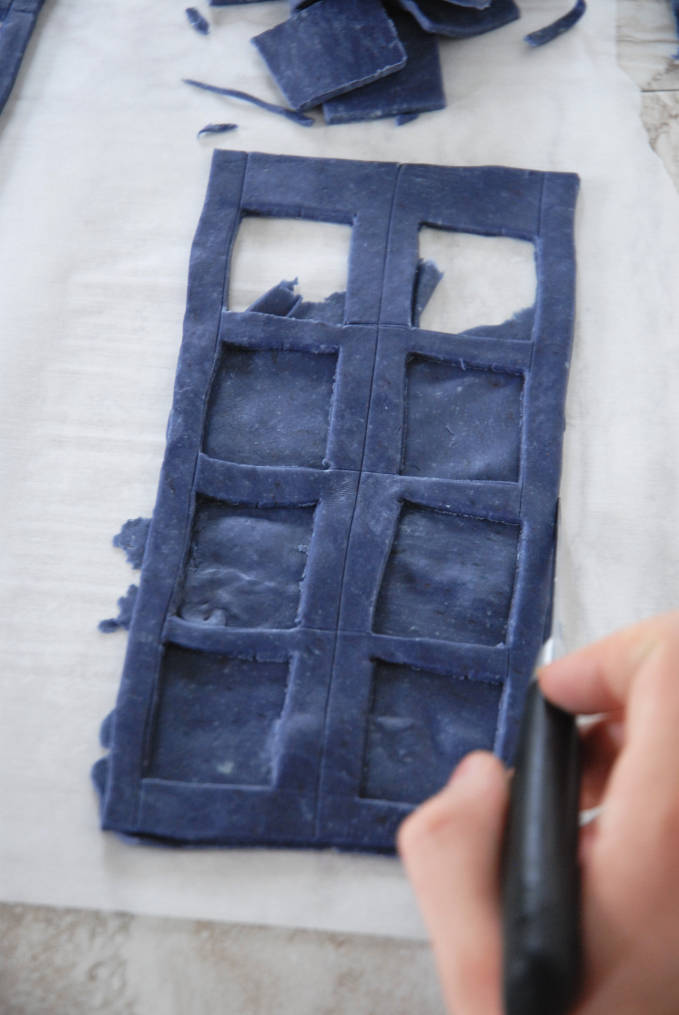 Trimming edges of Doctor Who TARDIS cake sides--click to see the full photo tutorial so YOU CAN MAKE YOUR OWN DOCTOR WHO TARDIS CAKE! #diy