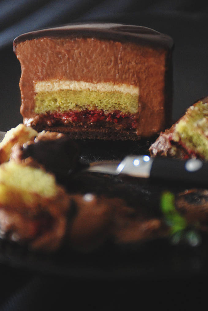 Ambroisie cake with biscuit joconde au chocolat, biscuit aux pistaches, homemade raspberry jam, dark chocolate mousse, pistachio mousse, and mirror glaze. Click to get the mouthwatering recipe!