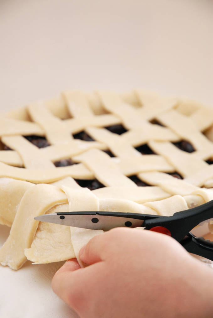 Cutting off extra pie dough ensures a nice edge--click to get a step-by-step photo tutorial on lattice pie crusts, so you can make them easily!