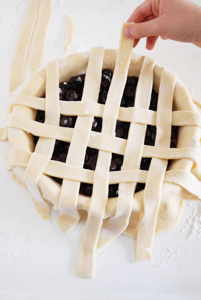Adding strips of pie dough to a pie to make a lattice crust--click to get a step-by-step photo tutorial on lattice pie crusts, so you can make them easily!