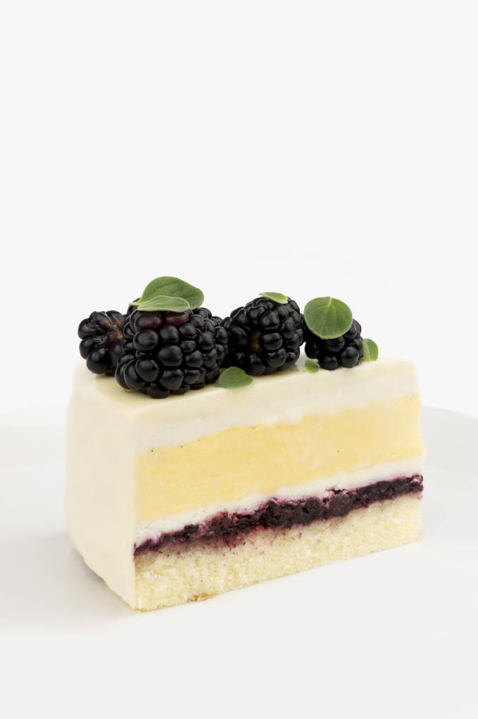 Blackberry, honey, and saffron entremet cake with sponge, honey simple syrup, blackberry coulis, honey mousse, saffron crème brûlée, and a white chocolate glaze.