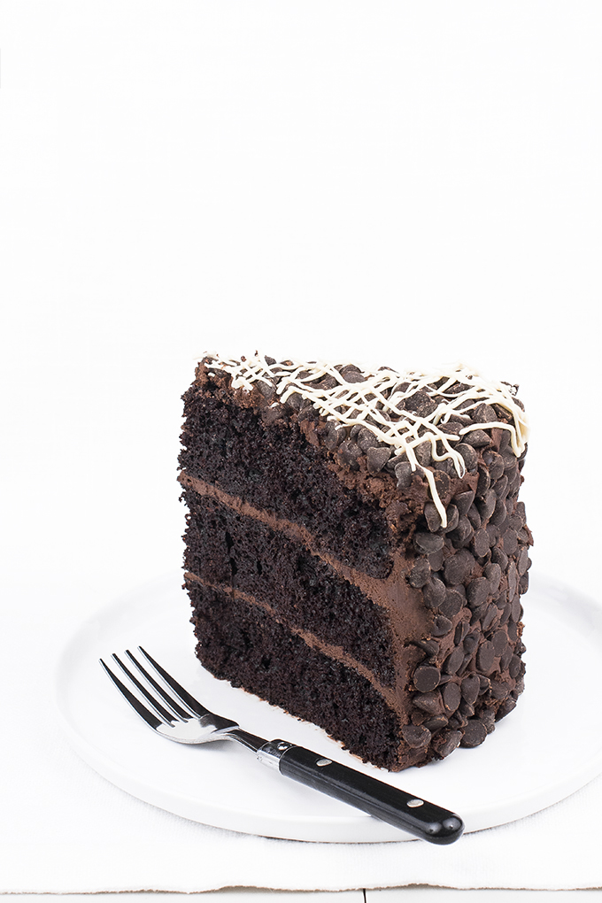Chocolate cake with chocolate-cream cheese frosting rolled in chocolate chips and drizzled with white chocolate.