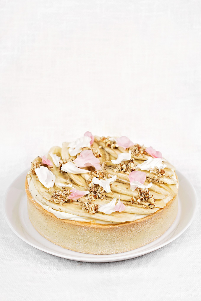 Banana cream tart with edible flowers and pecans