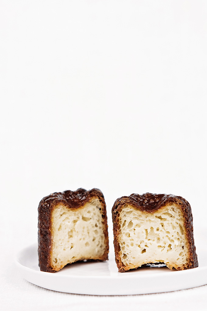 Traditional canelés (cannelés) with dark rum and Tahitian vanilla split in half to show custardy interior